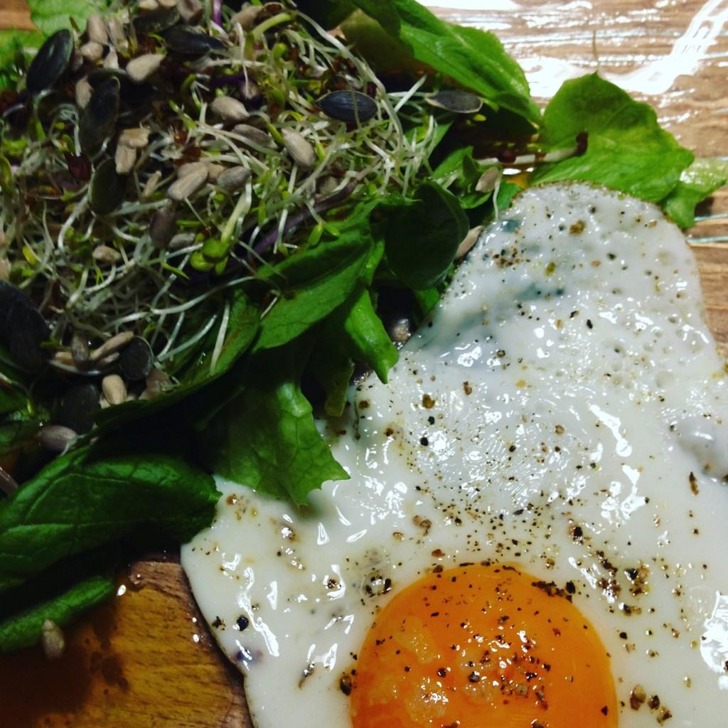 Petit déjeuner salé oeuf au plat et salade verte avec pousses germées, graines et vinaigrette oméga 3